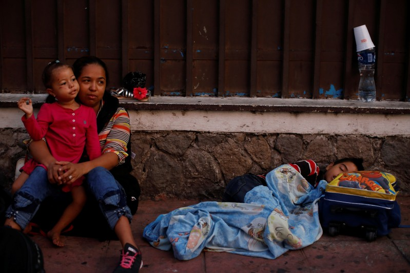 Honduran migrants wait to enter the Mexican Comission for Refugee Assistance (COMAR) in Tapachula