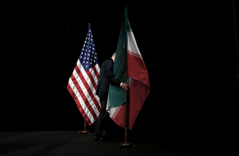 FILE PHOTO: A staff member removes the Iranian flag from the stage after a group picture with foreign ministers and representatives during the Iran nuclear talks at the Vienna International Center in Vienna