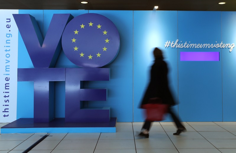 A woman walks past an advertising board for the EU elections at the Schuman railway station near the European Parliament in Brussels