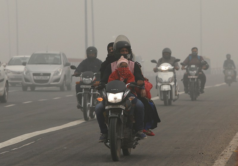 FILE PHOTO: People commute on a smoggy morning in New Delhi