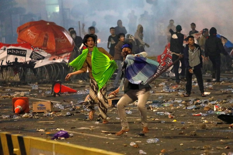 Protesters hurl stones during a riot near the Election Supervisory Agency (Bawaslu) headquarters in Jakarta