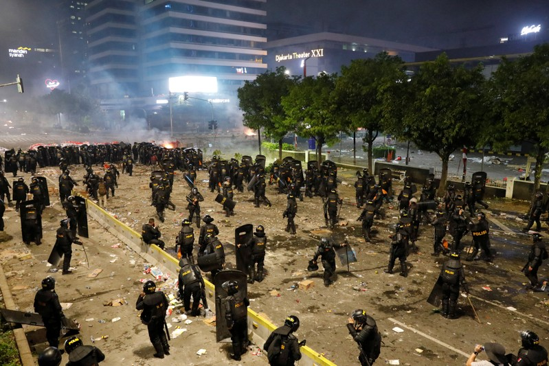 Riot police officers guard during a riot near the Election Supervisory Agency (Bawaslu) headquarters in Jakarta