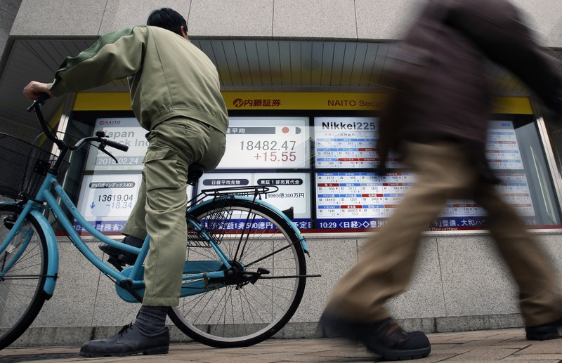 FILE PHOTO: A man riding on a bicycle looks at an electronic board showing the Japan's Nikkei average outside a brokerage in Tokyo