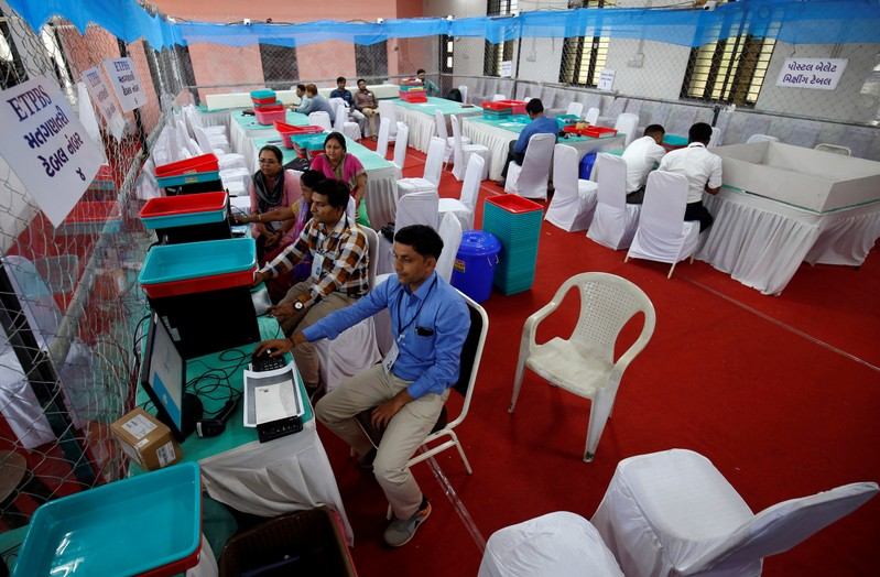 Election staff members work on their computers in a vote counting centre in Ahmedabad