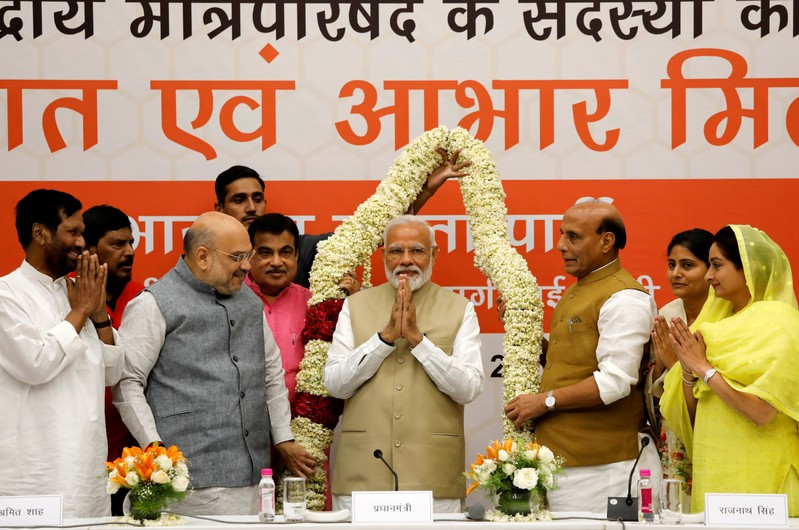 FILE PHOTO: India's PM Modi gestures as he is presented with a garland during a thanksgiving ceremony by BJP leaders to its allies at the party headquarters in New Delhi,