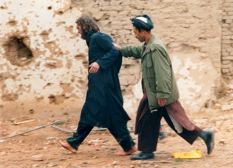 FILE PHOTO: U.S.-born John Walker Lindh is led away by a Northern Alliance soldier after he was captured near Mazar-i-Sharif