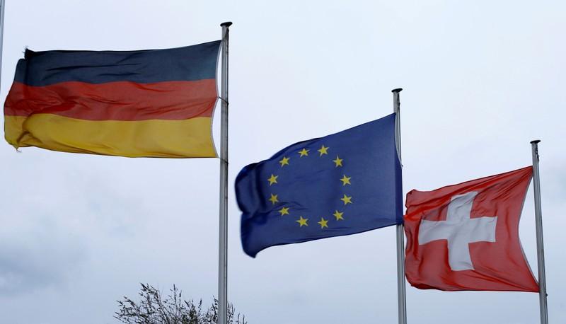 FILE PHOTO: An EU flag flies between Swiss and German national flags near the German-Swiss border in Rheinfelden, Germany