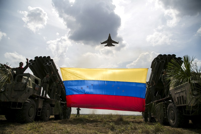 FILE PHOTO: A Russian-made Sukhoi Su-30MKV fighter jet of the Venezuelan Air Force flies over a Venezuelan flag tied to missile launchers, during the