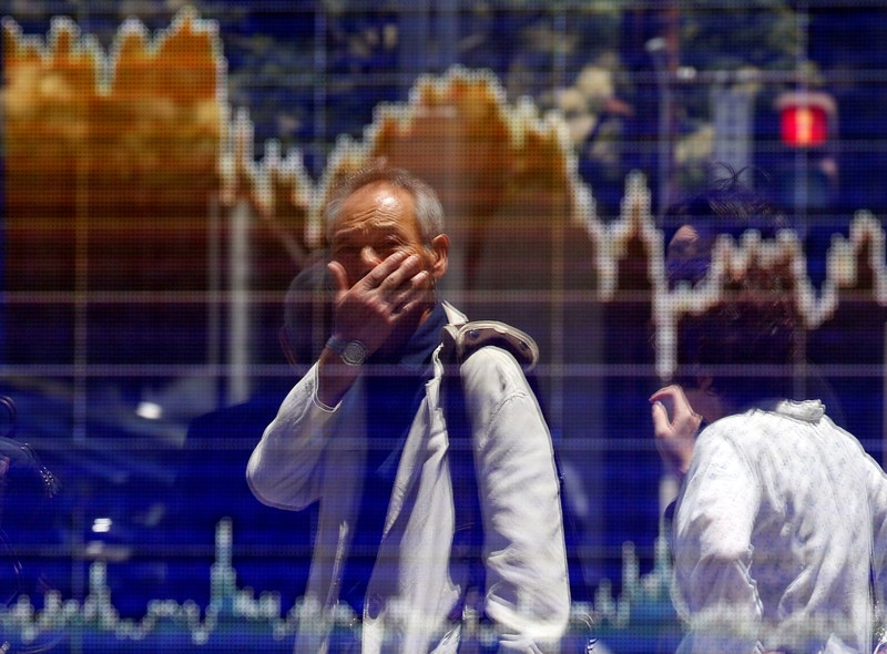 FILE PHOTO: A man is reflected in an electronic board showing the graph of the recent fluctuations of the TOPIX outside a brokerage in Tokyo