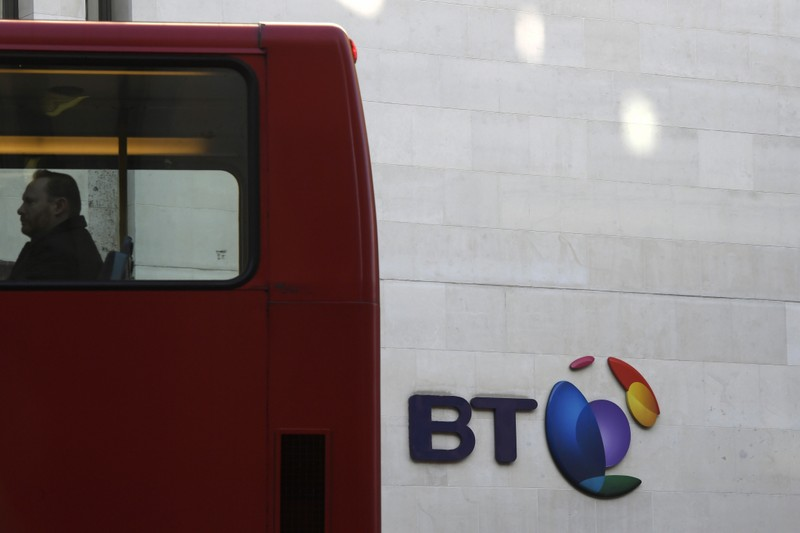 A bus passes a BT logo outside of offices in the City of London