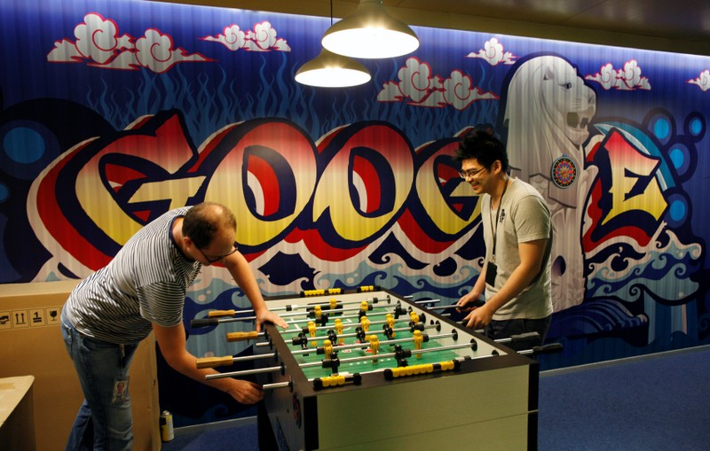 FILE PHOTO: Google's communications manager Moroney plays table soccer with a Google employee at a recreational area of their Singapore office