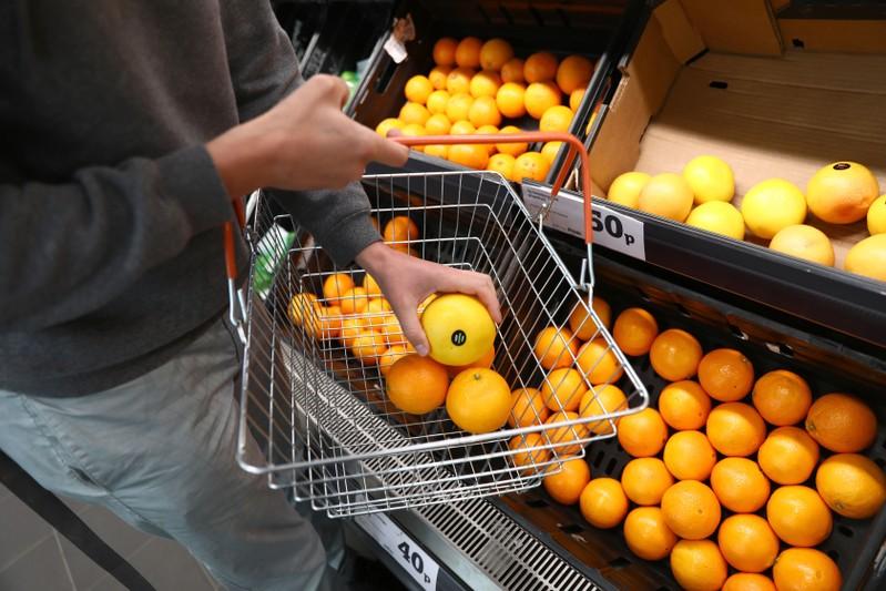 A shopper loads a basket in a supermarket in London