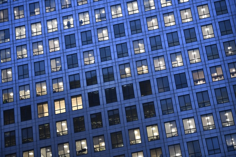 Office lights are on at dusk in the Canary Wharf financial district, London