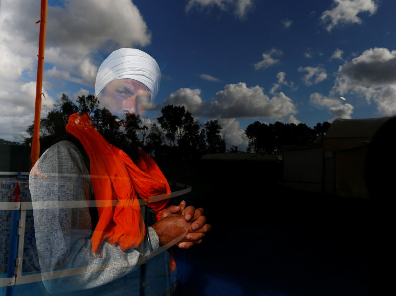 A Sikh migrant worker looks through a window of the temple in Borgo Hermada, in the Pontine Marshes, south of Rome