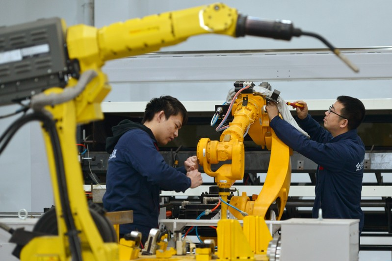 Men work on a production line manufacturing robotic arms at a factory in Huzhou, Zhejiang