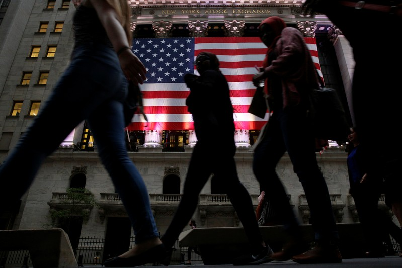 FILE PHOTO: People pass by the NYSE in the financial district of New York