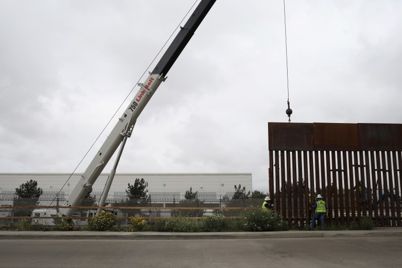Workers replace a section of the border fence between U.S. and Mexico, as seen from Tijuana