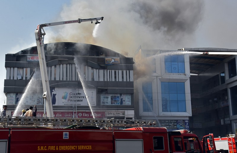 Firefighters douse a fire that broke out in a four-story commercial building in Surat