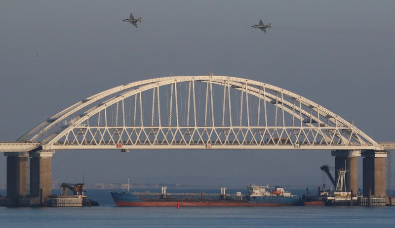 Russian jet fighters fly over a bridge connecting the Russian mainland with the Crimean Peninsula with a cargo ship beneath it after three Ukrainian navy vessels were stopped by Russia from entering the Sea of Azov via the Kerch Strait in the Black Sea