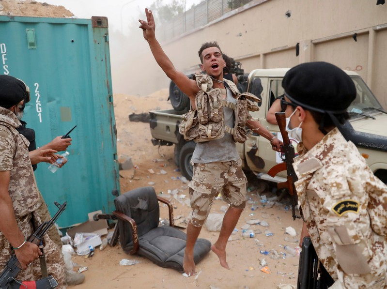 A fighter loyal to Libya's U.N.-backed government (GNA) gestures during clashes with forces loyal to Khalifa Haftar on the outskirts of Tripoli