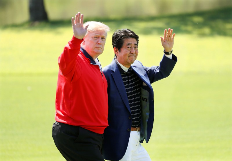 U.S. President Donald Trump and Japanese Prime Minister Shinzo Abe wave on the way to the course to play golf at Mobara Country Club in Mobara, Chiba Prefecture