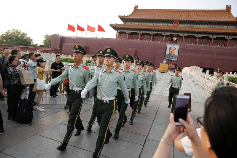 People take pictures of paramilitary officers marching in formation in Tiananmen Square in Beijing