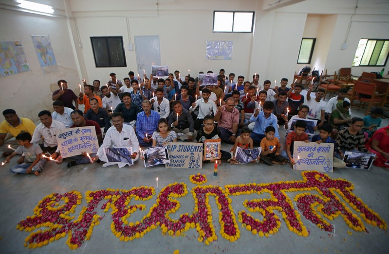 People attend a prayer meet to pay tribute to the victims of a fire that broke out in a commercial building in the western city of Surat on Friday, inside a library in Ahmedabad