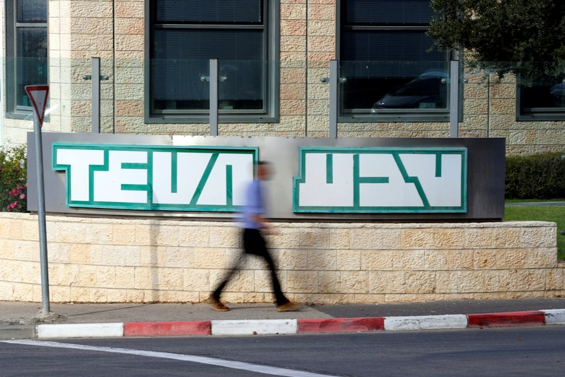 A man walks past the logo of Teva Pharmaceutical Industries at their plant in Jerusalem