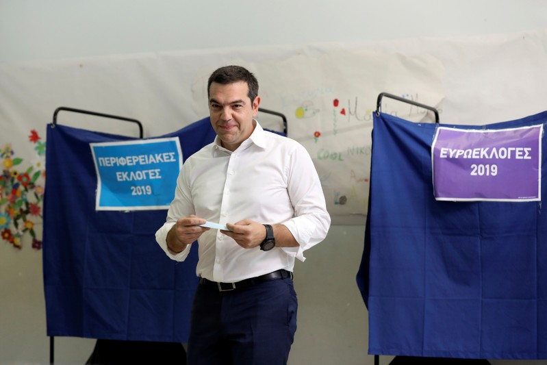 Greek PM Tsipras holds his ballot before voting for the European and local elections at a polling station in Athens