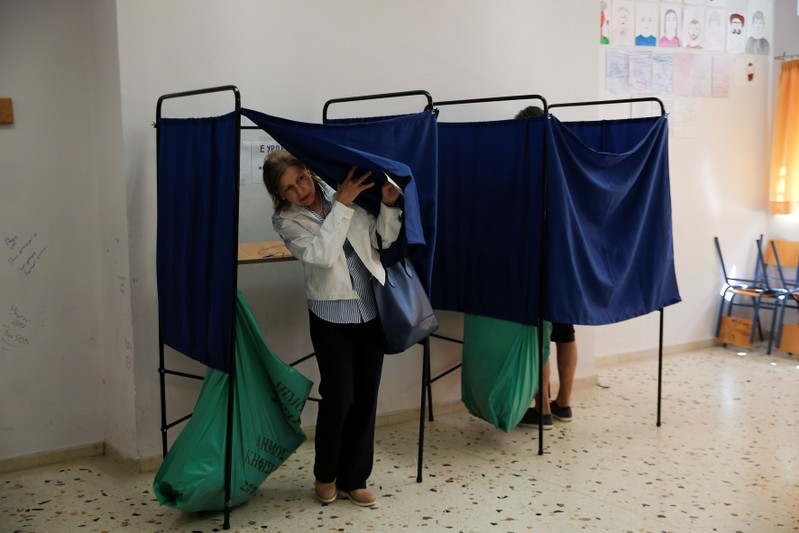A woman exits the polling booth before casting her vote for the European and local elections at a polling station in Athens