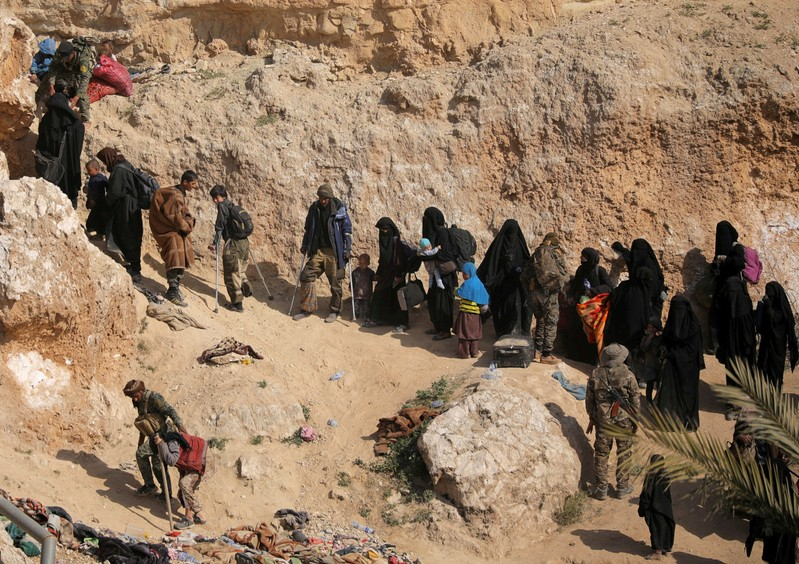 FILE PHOTO: Islamic state fighters and their families walk as they surrender in the village of Baghouz, Deir Al Zor province