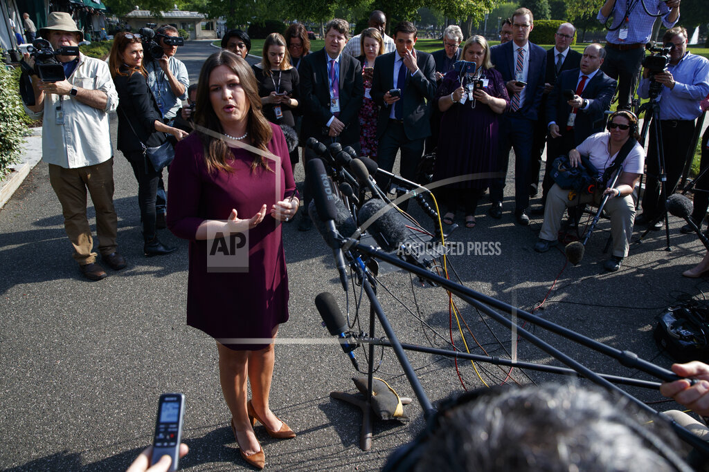 White House press secretary Sarah Sanders talks with reporters outside the White House Thursday