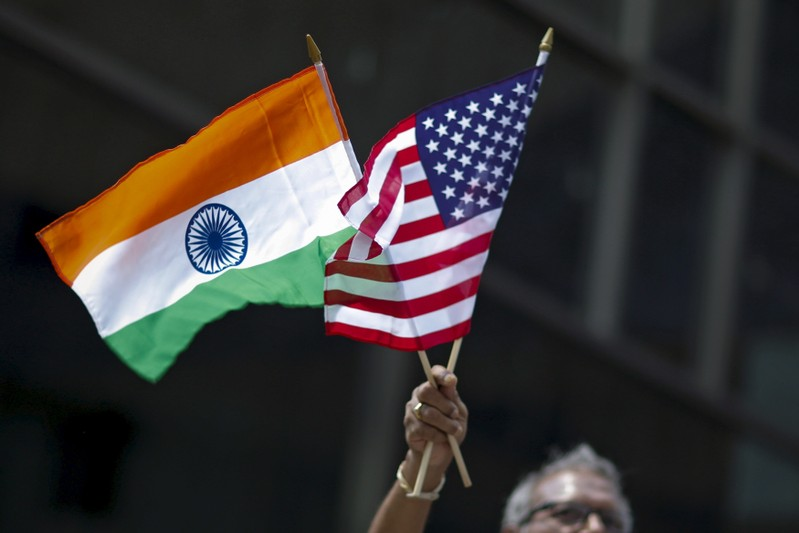 Man holds the flags while people take part in the 35th India Day Parade in New York
