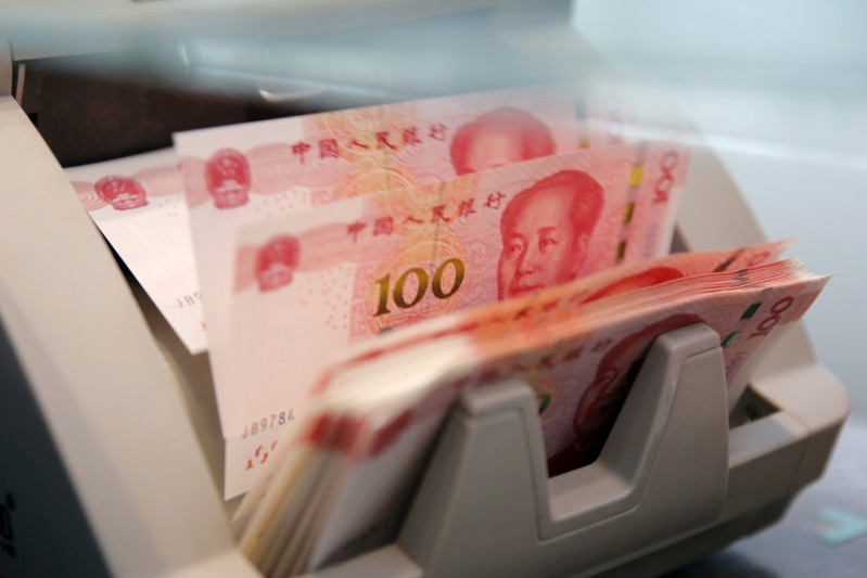 FILE PHOTO: Chinese 100 yuan banknotes in a counting machine while a clerk counts them at a branch of a commercial bank in Beijing