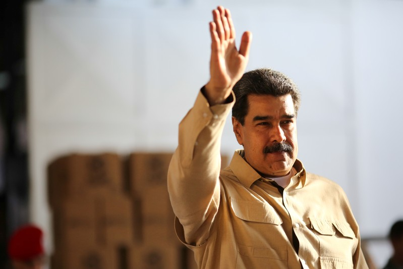FILE PHOTO: Venezuela's President Nicolas Maduro waves during his visit to a packing center of the CLAP (Local Committees of Supply and Production) program, a Venezuelan government handout of basic food supplies, in Caracas