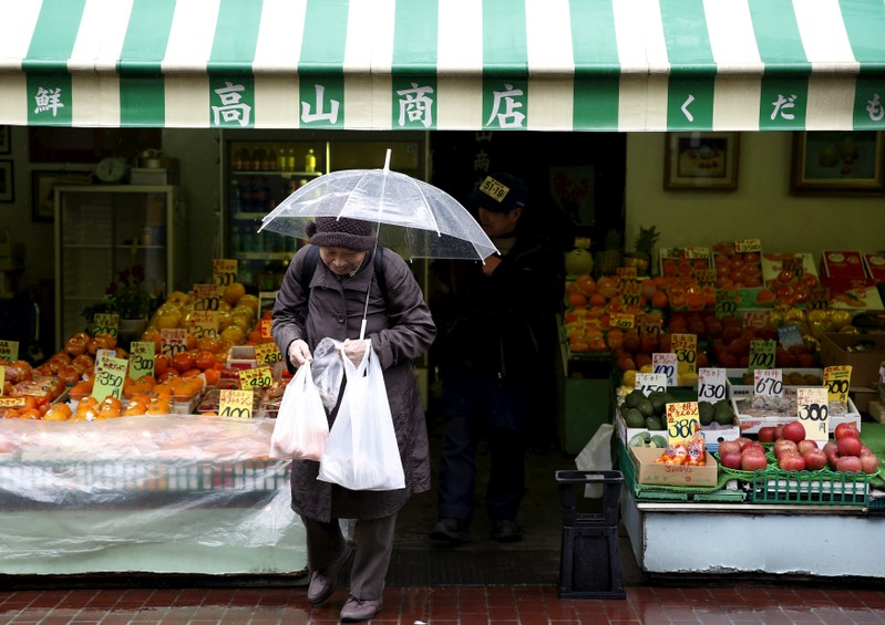 FILE PHOTO: A shopper holding plastic bags walks out from a greengrocer's at Tokyo's Sugamo district, an area popular with the Japanese elderly, in Tokyo