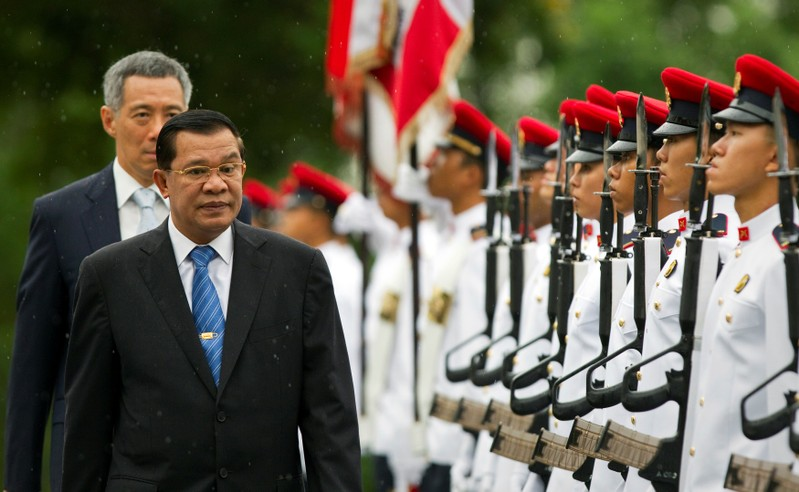 FILE PHOTO: Cambodia's PM Hun Sen inspects an honour guard as Singapore's PM Lee Hsien Loong walks behind him at the Istana in Singapore