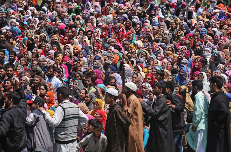 People watch the body of Imran Ahmad Bhat, a suspected militant, who was killed during a gun battle with Indian security forces today, during his funeral procession in Arihal village in South Kashmir's Pulwama