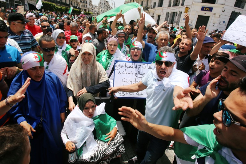 Demonstrators chant slogans during a protest demanding the removal of the ruling elite in Algiers