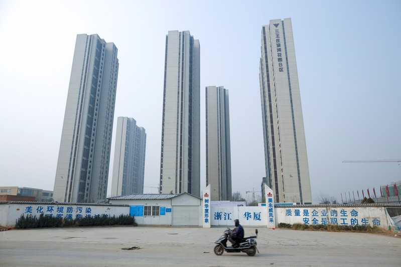 A man rides a scooter past apartment highrises that are under construction near the new stadium in Zhengzhou
