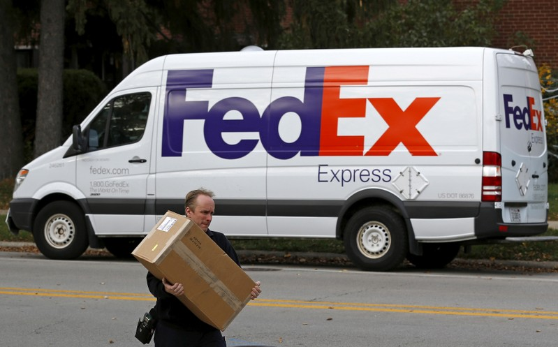 FILE PHOTO: A FedEx delivery worker carries a package for a delivery in Wilmette