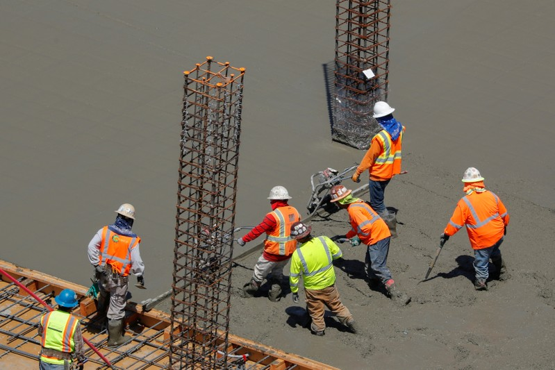 FILE PHOTO: Workers pour cement at a construction site for an office town in downtown San Diego