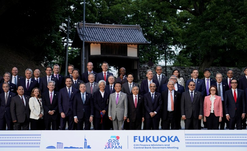 Japan's Finance Minister Taro Aso poses next to IMF Managing Director Christine Lagarde and Bank of Japan Governor Haruhiko Kuroda for a family photo during the G20 finance ministers and central bank governors meeting, in Fukuoka