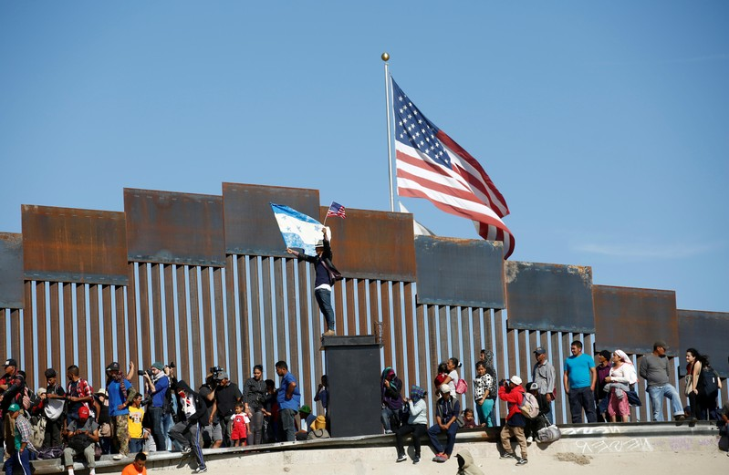 FILE PHOTO: A migrant, part of a caravan of thousands traveling from Central America en route to the United States, holds flags of Honduras and the United States in front of the border wall between the U.S. and Mexico in Tijuana