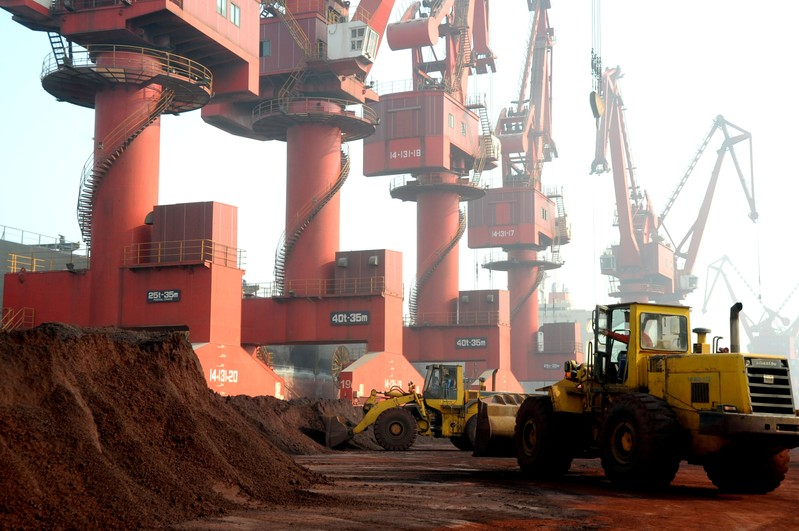 FILE PHOTO: Workers transport soil containing rare earth elements for export at a port in Lianyungang