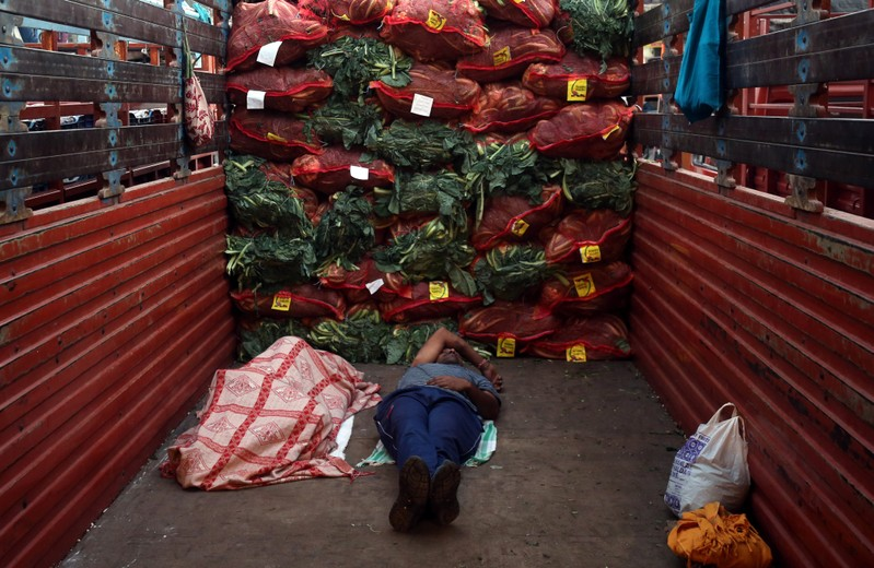 Men sleep in a supply truck loaded with sacks of cauliflower at a vegetable wholesale market in Mumbai