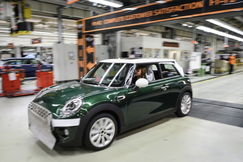 Workers assemble cars at the plant for the Mini range of cars in Cowley, near Oxford
