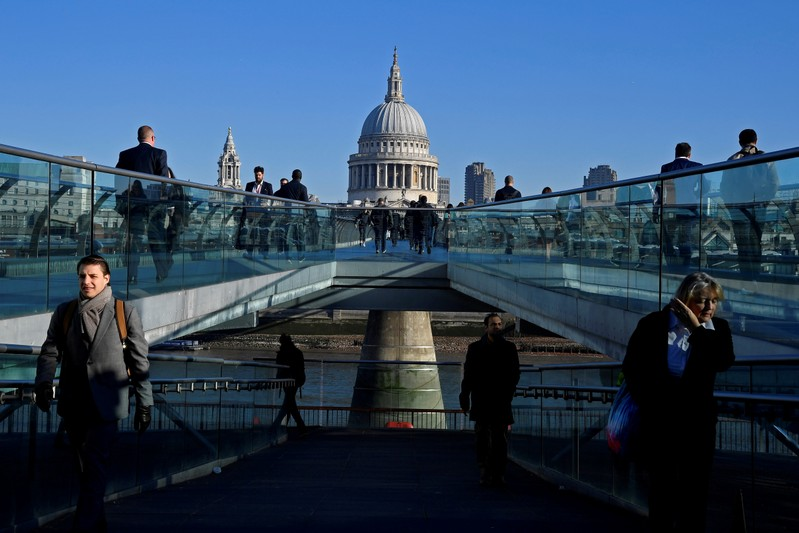 FILE PHOTO: Workers are seen crossing the Millennium Bridge, with St Paul's Cathedral seen behind during the morning rush hour in London