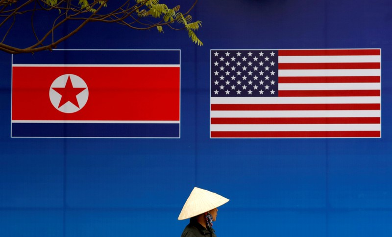 FILE PHOTO: A person walks past a banner showing North Korean and U.S. flags ahead of the North Korea-U.S. summit in Hanoi