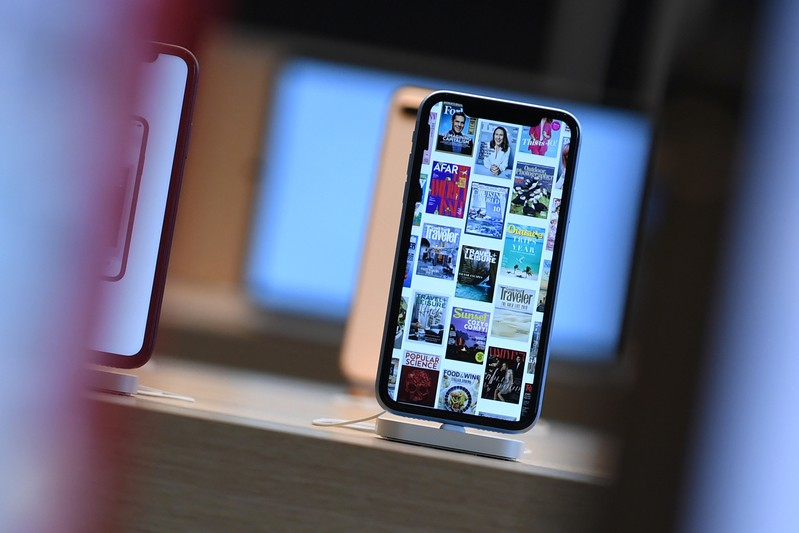 FILE PHOTO: Front pages of newspapers and magazines are displayed on an iPhone during the grand opening and media preview of the new Apple Carnegie Library store in Washington